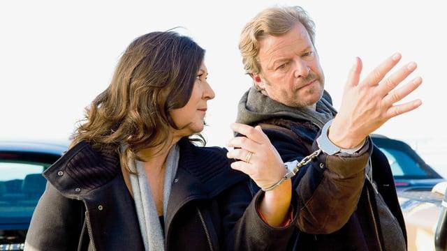 Eine Frau und ein Mann sind mit einer Handschelle zusammengekettet.