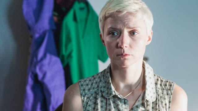 Eine blonde Frau mit kurzen Haaren. Im Hintergrund sind Kleidungsstücke zu erkennen.