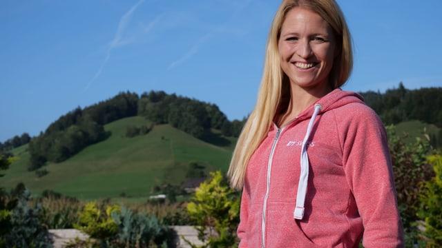 Eine Frau vor grünen Hügeln und blauem Himmel. Sie lacht.