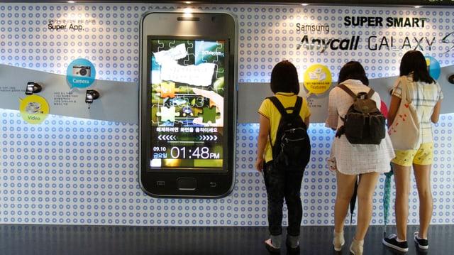 U-Bahn in einer asiatischen Stadt. Grosses Bild eines Smartphones, daneben warten Schülerinnen auf den Zug.