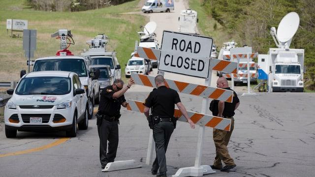 Die Polizei sperrt die Strasse, die zu einem Tatort führt.