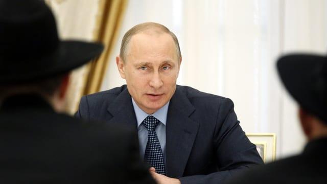Putin sitzt zwei Männern mit Hut gegenüber und spricht mit ihnen.