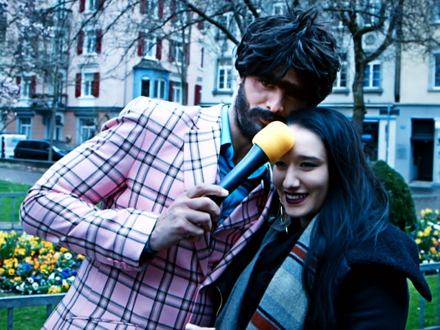 Müslüm drückt Interviewpartnerin das Mikrofon an die Stirn.