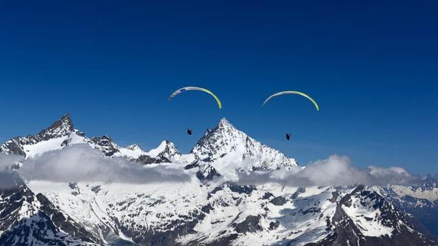 Zwei Gleitschirmflieger mit Bergen im Hintergrund.
