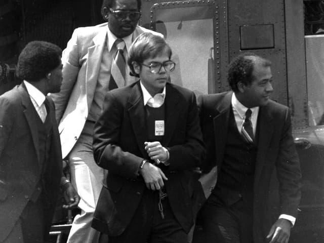 Hinckley wird in Handschellen auf eine Militärbasis gebracht. Drei Männer begleiten ihn aus dem Helikopter.