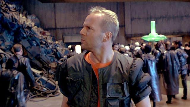 Bruce Willis geht durch eine Halle an einem Müllberg vorbei.