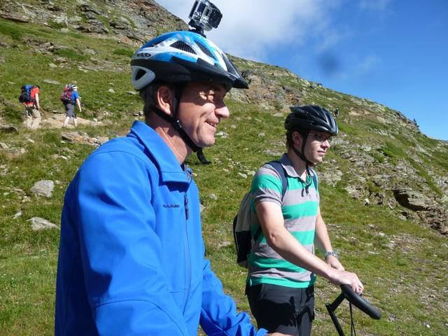 Zwei Männer stehen mit ihren Trottinetten in einer Berglandschaft. Einer hat eine Kamera an seinem Helm.