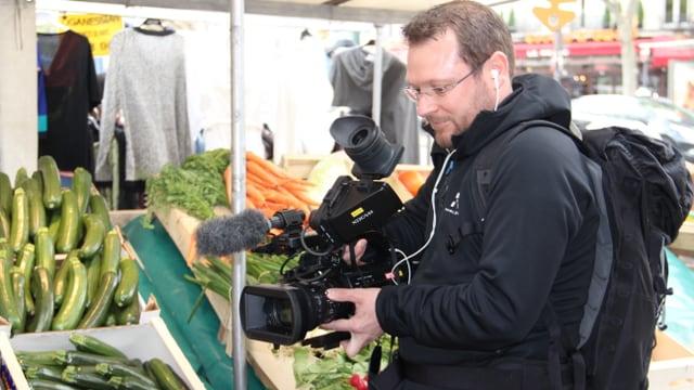 Purtret da Stefan Dobler. El filmescha cun ina camera da VJ ina fiera. Davostiers in stand cun legums.