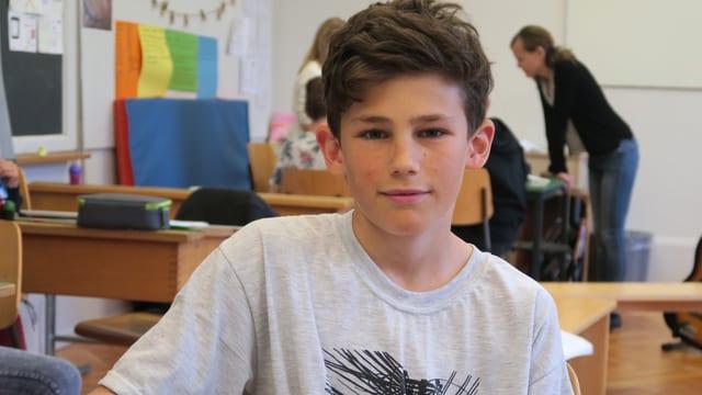 Lennox sitzt am Pult im Klassenzimmer.