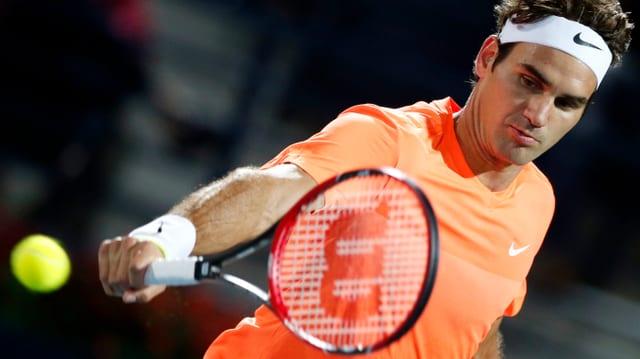 Roger Federer en in t-shirt oransch cun in rachet da tennis enta maun.