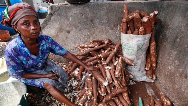 Eine Frau in Nigeria sitzt vor einem Haufen Maniok-Knollen.