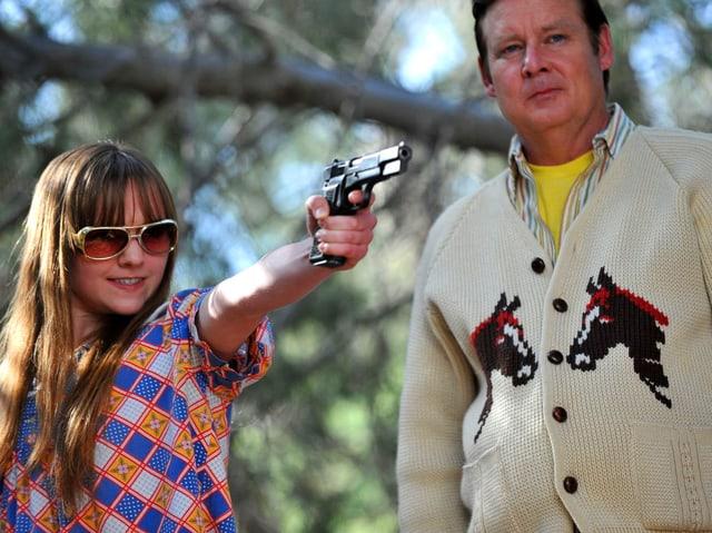 Mädchen zielt mit Pistole, Mann steht daneben