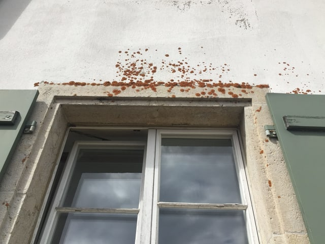 Schäbige Fassade oberhalb eines Fensters
