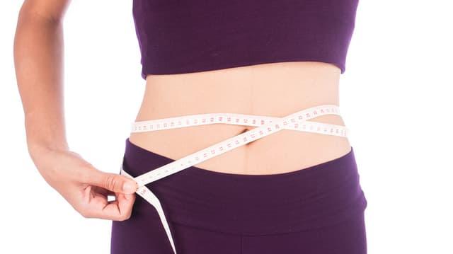 Eine Frau misst mit einem Massband ihren Bauchumfang.