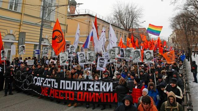 Demonstranten mit Fotos und Fahnen