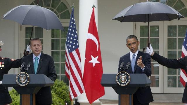 Obama und Erdogan unter Schirmen.