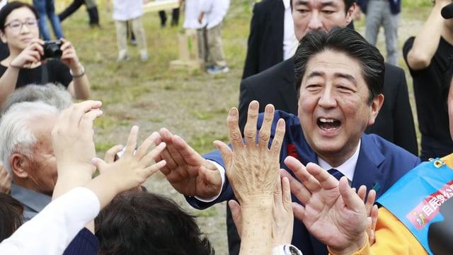 Abe lacht und greift nach ihm entgegengestreckten Händen aus dem Publikum.