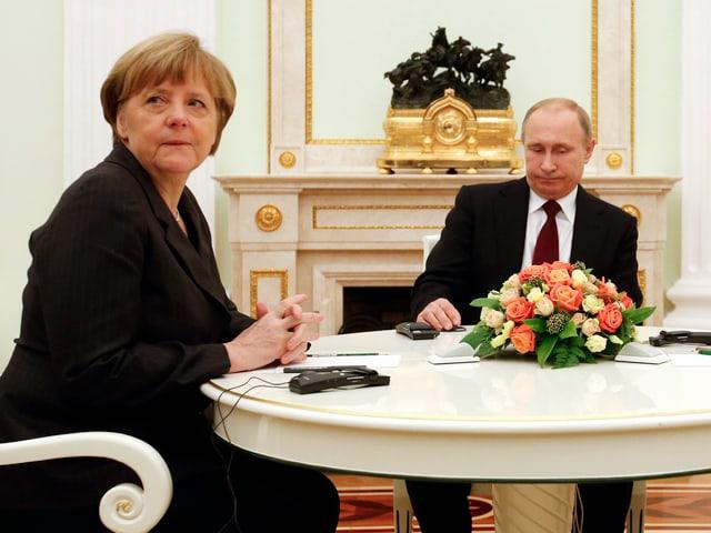 Am Runden Tisch: Bundeskanzlerin Angela Merkel blickt Ritchtung Kamera, Putin auf den Tisch.