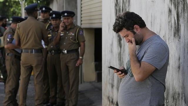 Ein Tourist schaut auf sein Smartphone, im Hintergrund Männer in Uniform.