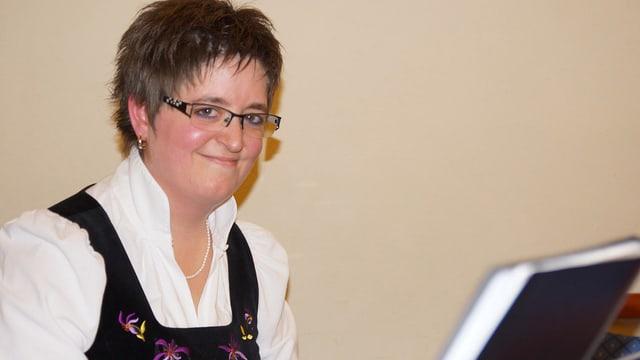 Eine junge Frau mit kurzen dunklen Haaren und Brille sitzt an einem Piano.
