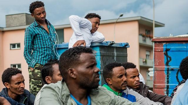 Junge Eritreer in einem Asylempfangszentrum sitzen auf dem Boden.