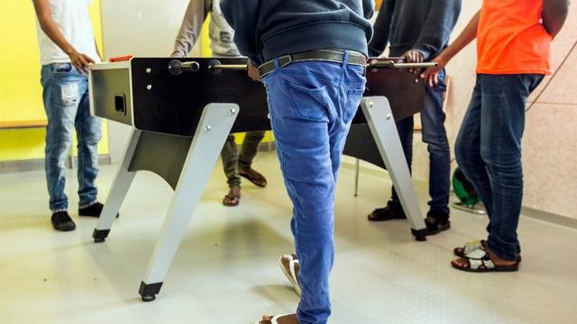 Asylbewerber stehen um einen Tischfussballkasten herum