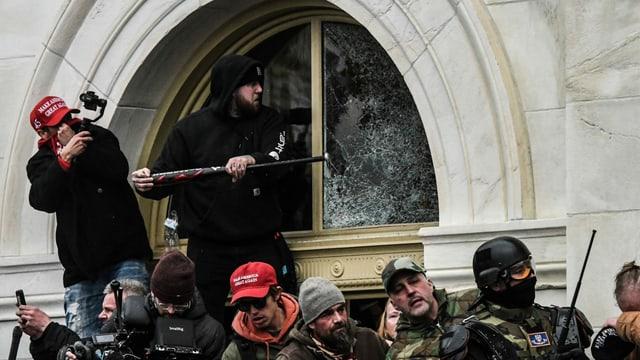 Ein Trump-Supporter schlägt beim Sturm aufs Kapitol ein Fenster mit einem Baseballschläger ein.