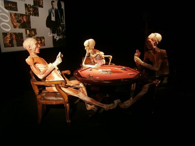Plastinierte Leichen spielen an einem Tisch Karten.