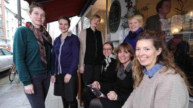 Sieben Frauen sitzen und stehen vor einem Café.