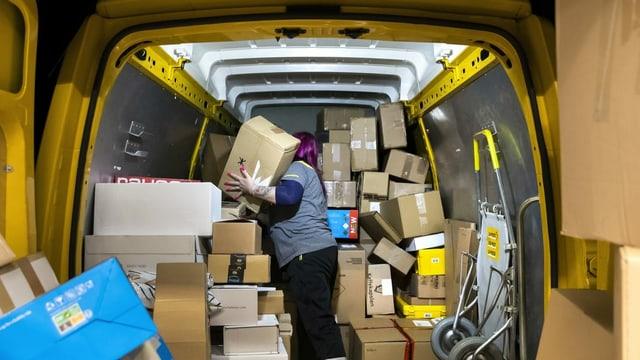 Ina collavuratura da la Posta Svizra sortescha ils pachets en l'auto da transport.