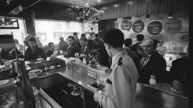 eine schwarz-weiss Aufnahme einer Theke, mit vielen Gästen und einem Mann, der sie bedient