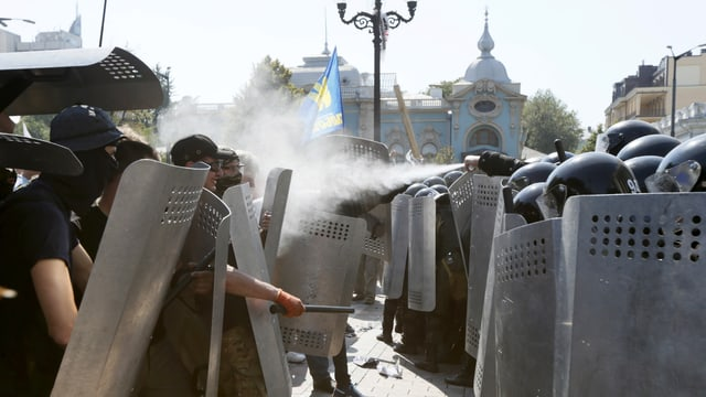 Beide Lager stehen sich dicht an dicht. Die Polizei sprüht Wasser auf die Demonstranten.
