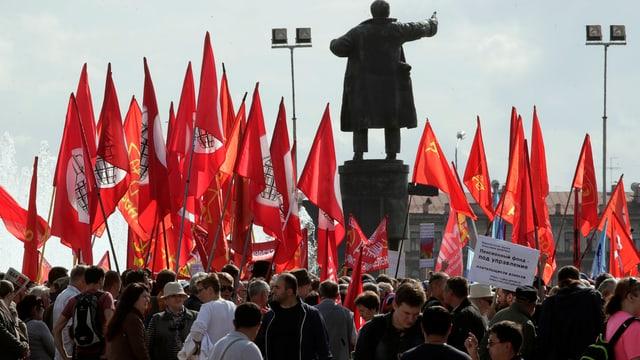 Demonstranten stehen um eine Lenin-Statue