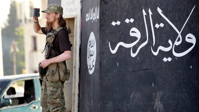 Das Bild zeigt einen westlichen Kämpfer in Syrien, der nebem einer an einer Hauswand aufgemalten Flagge der Terrorgruppe Islamischer Staat posiert. (Bild vom Juni 2014, Reuters)