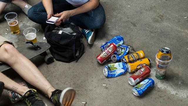 Beine zweier junger Leute, viele Bierdosen am Boden.