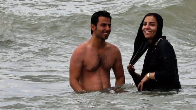 Der Mann trägt kein Oberteil, seine Frau ist bis zum Gesicht verschleiert. Sie lüftet leicht ihr Kopftuch.