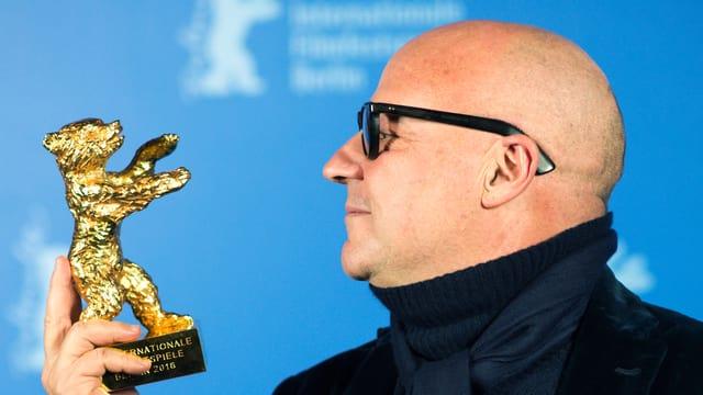 Ein Mann mit Glatze und schwarzer Brille hält die Statue eines goldenen Bären in der Hand.