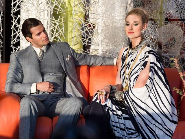 Ein Mann und eine Frau sitzen auf einer Couch.