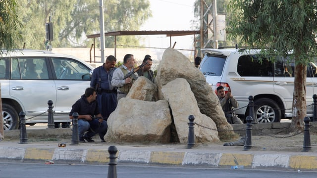 Männer mit Gewehren verschanzen sich hinter Steinen