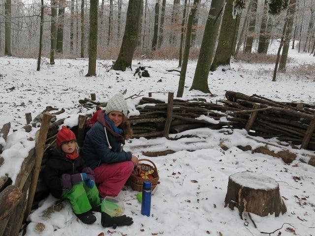 Waldsofa mit Betreuerin und Kindern.