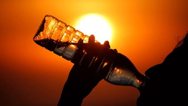 Person trinkt Wasser aus einer Petflasche.