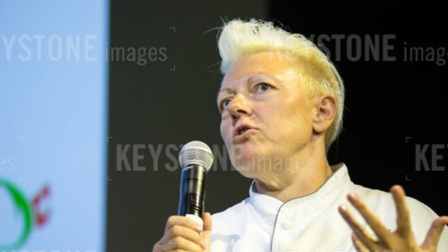 Eine Frau, mit kurzen blonden Haaren und einem Mikrofon in der Hand.