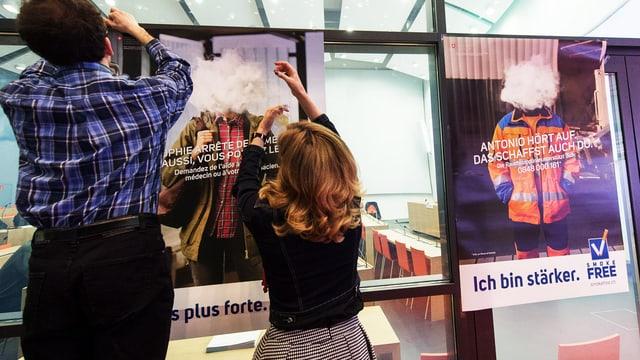 Ein Mann und eine Frau hängen Plakate der 2015er-«Smokefree»-Kampagne auf.