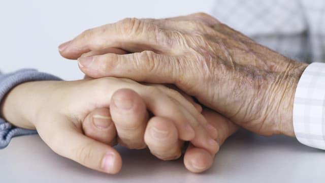 Eine Hand hält eine andere.