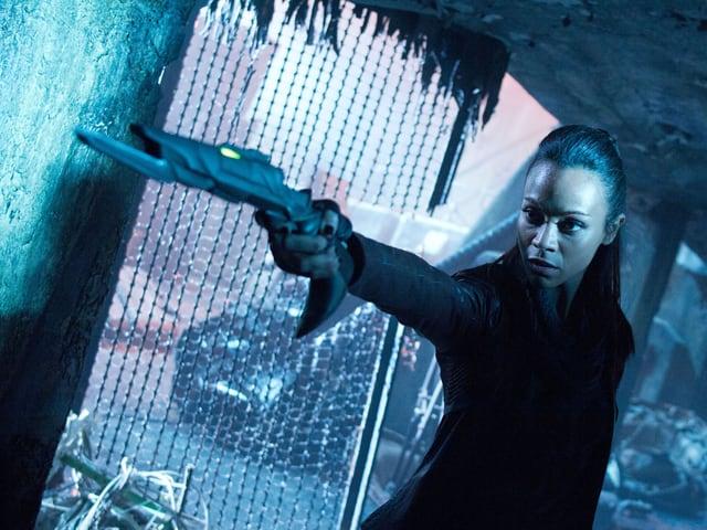 Lieutenant Uhura mit Phaser in der Hand.
