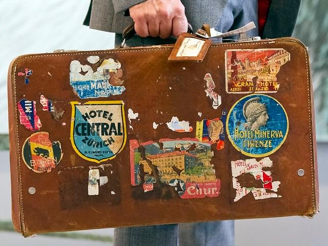 Ein alter brauner Koffer. Darauf sind verschiedene Kleber aus verschiedenen Städten Europas.