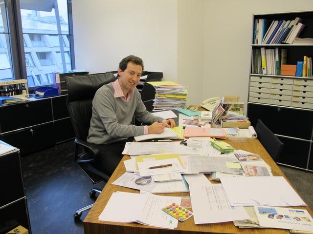 Ein Mann in grauem Pullover und rosa Hemd sitzt an einem Tisch mit vielen Dokumenten.