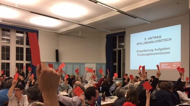 Viele Menschen in einem Saal, die rote Zettel in die Luft strecken.