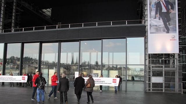 Menschen, teils in roten Jacken, vor dem KKL Luzern