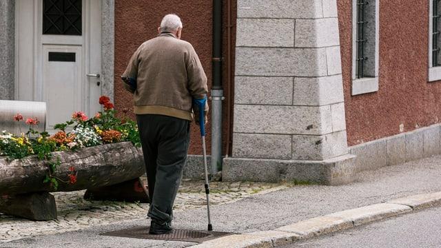 Alter Mann geht am Stock auf einem Trottoir